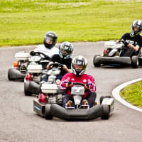 A group of guys racing go karts around a track