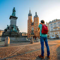 Male tourist with backpack photographing famous Polish basilica in the center of Krakow