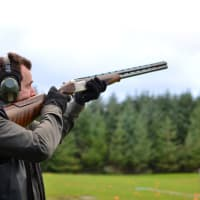 A man shoots a shotgun during clay pigeon shooting