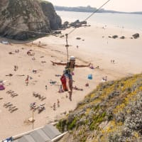 A woman on a zip line over Lusty Glaze beach Newquay