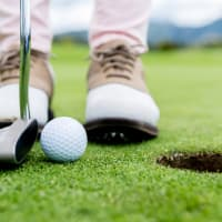 A golf putts a ball into a hole