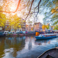 Spring scene in Amsterdam city tours by boat on the famous Dutch canals