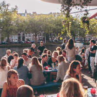 Waterkant Amsterdam during busy day time people enjoying drinks