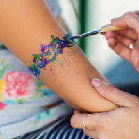 girl getting arm glitter decoration