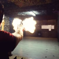 A man shoots a gun a shooting range sharper