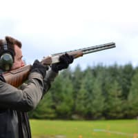 A man doing clay pigeon shooting