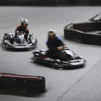 Two drivers race around a track in go karts