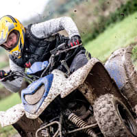 A muddy man on a quad bike
