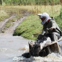 A man riding a quad bike through a river