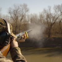 a man shoots during clay pigeon shooting