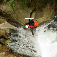 man jumping from cliff whilst canyoning