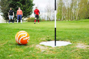 A group of men playing foot golf