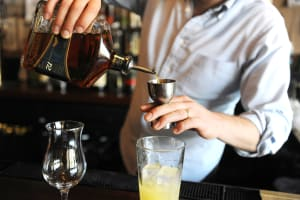 A man pouring a cocktail during a cocktail making class