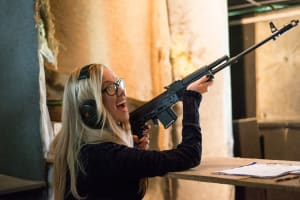 A woman shooting a machine gun AK47