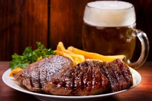 A plate of steak and a pint of beer