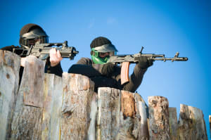 Two men hiding behind a wall playing airsoft