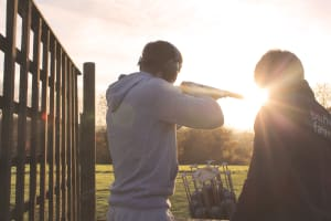 A man shooting clays with a shotgun in the sun