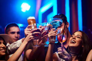 Group of Young and Friendly People Toasting in Nightclub