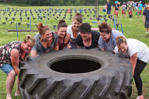A smiling hen party lift a tire playing highland games
