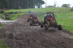 A stag group racing off road go karts on a muddy track