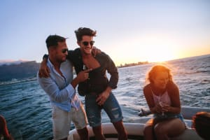 group of friends on boat with sunset stags having fun