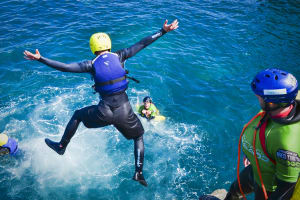man jumping from cliff coasteering flip