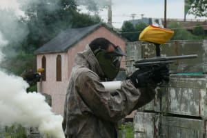 Two men playing paintball with smoke grenade