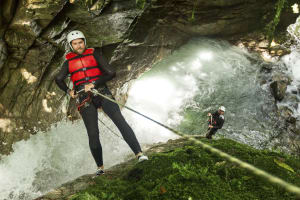 a man abseils from a cliff whilst canyoning