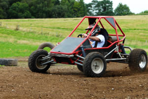 A man race a rage buggy around a track