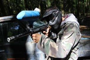 A man plays paintball in the woods