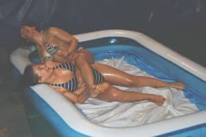 Two wrestling babes wrestling in a pool