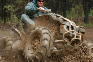 A man drives a quad through the mud