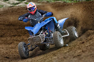 Quad bike racing through mud