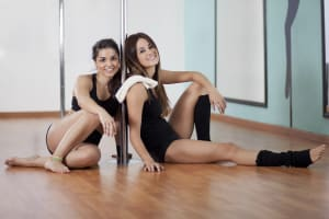 Two women taking a pole dancing class