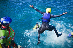 man jumping from cliff coasteering