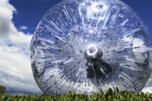 An image of a person rolling down a hill in a zorb ball
