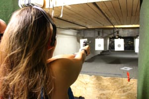 A woman firing a pistol