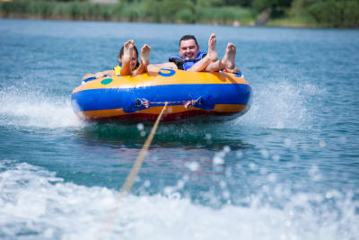 Two people on a ringo behind a speedboat