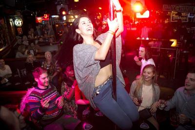 A woman dances on the bar during a bar crawl