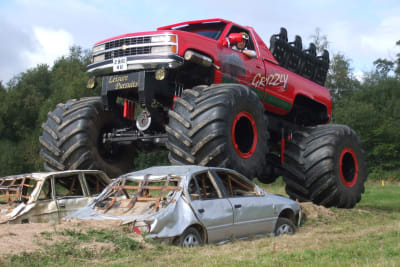 A monster truck driving over cars