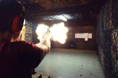 A man shoots a gun a shooting range