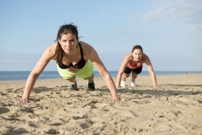 Two women doing exercise on the beach during bootcamp