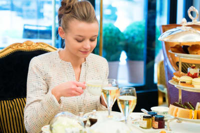 An attractive woman having a champagne afternoon tea