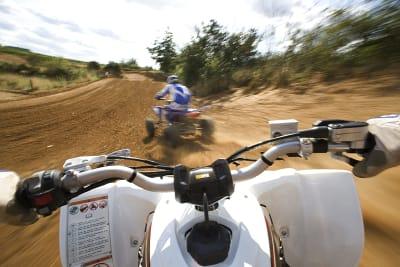 Two men racing quad bikes around a dirt track