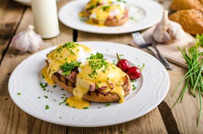 Eggs Benedict with little salad, milk and fresh herbs_brunch_breakfast