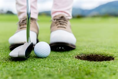 A golf putts a ball into a hole