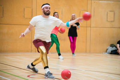 A man throwing a ball during a game of dodgeball