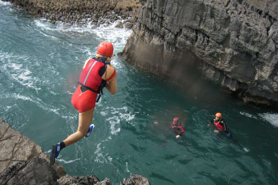 A stag group jumping from a cliff during coasteering
