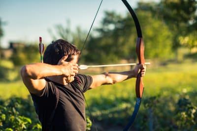 a man fires a bow and arrow