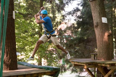 A man on a high ropes course in woodland flipped
